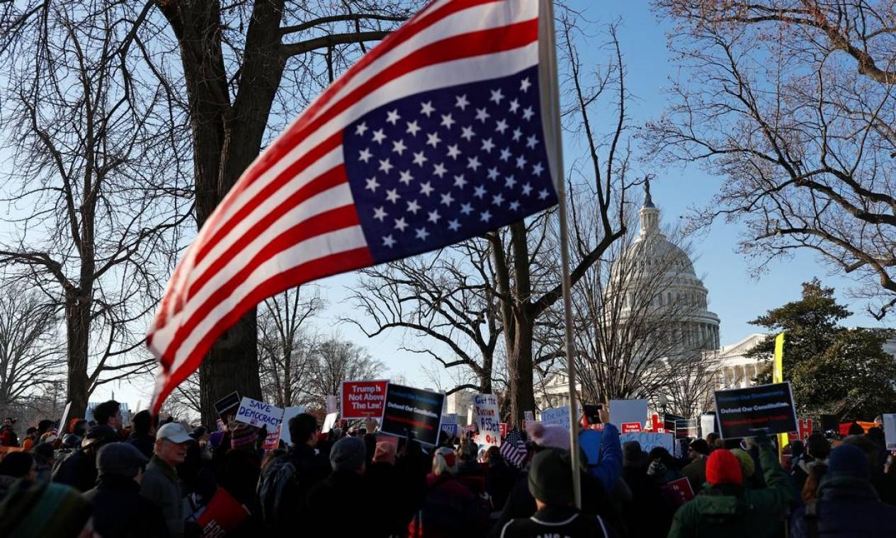 Ativistas protestam com bandeira dos EUA de ponta-cabeça para pedir o impeachment de Donald enquanto o Congresso debate o processo antes da votação Foto: Tom Brenner / Reuters
