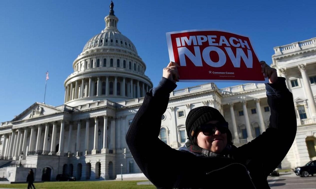 """Uma mulher segura um cartaz escrito """"impeachment agora"""" em frente ao Capitólio, em Washington, onde deputados votam o processo em que Trump é acusado de abuso de poder e obstrução do Congresso Foto: Olivier Douliery / AFP"""