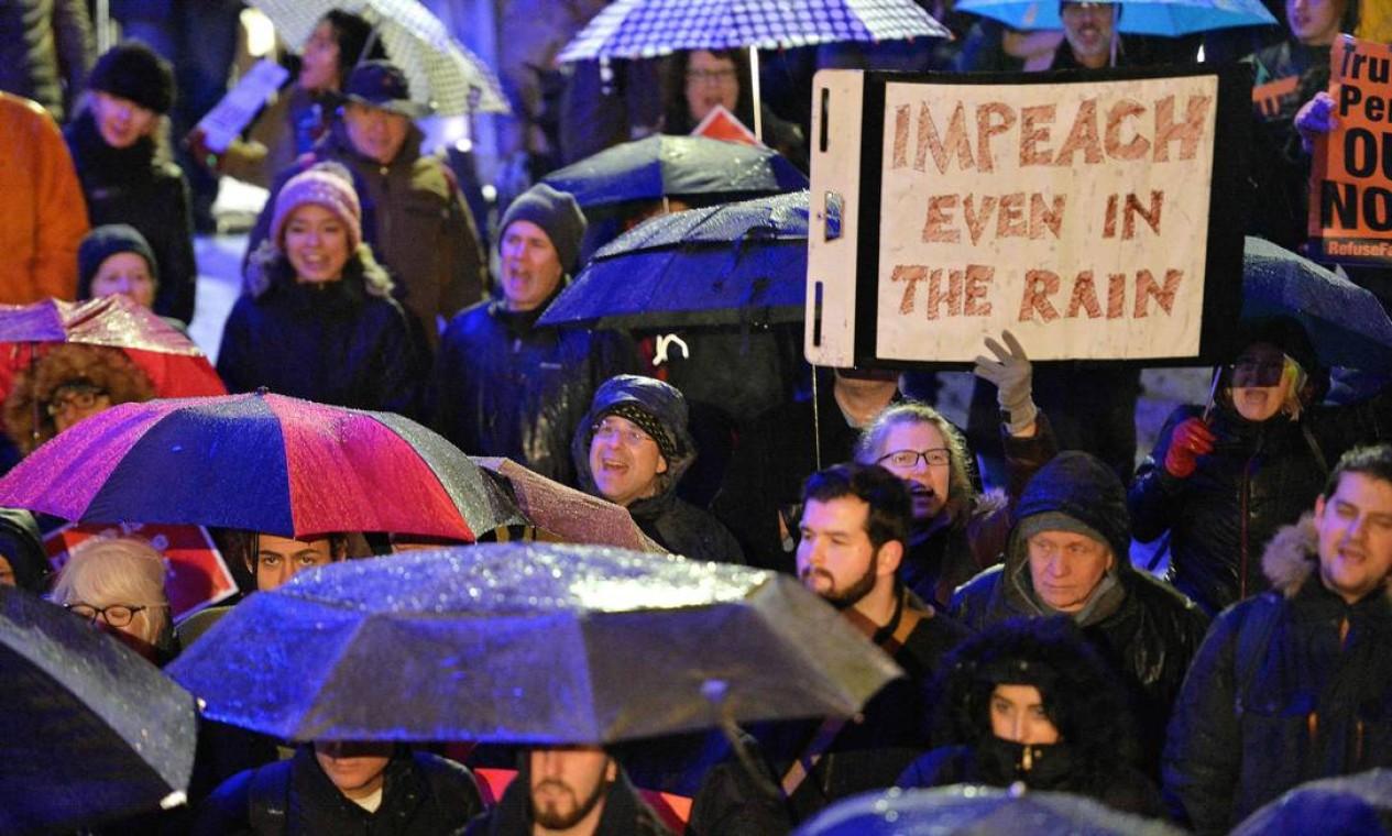 """Impeachment até na chuva"", diz o cartaz da manifestante no parque Boston Common, no estado de Massachusetts Foto: Joseph Prezioso / AFP"