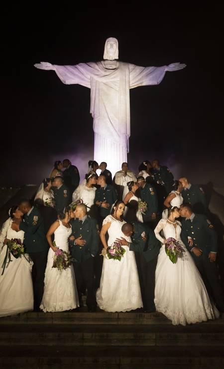Enfim, casados. Casais se beijam aos pés do Cristo Redentor, enquanto o PM Leandro Vieira, dá um selinho na barriga da esposa Rosana, grávida de cinco meses Foto: Leo Martins / Agência O Globo