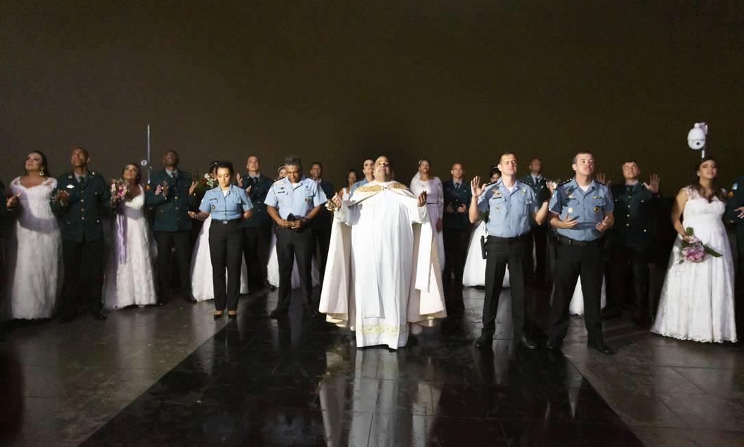 Oficiais da PM e os casais de noivos pedem a bênção de Cristo. A cerimônia religiosa foi celebrada pelo reitor do santuário, padre Omar Raposo Foto: Leo Martins / Agência O Globo