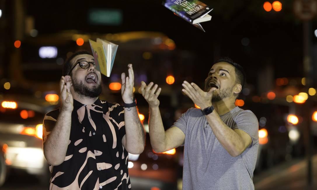 Os escritores Vitor Martins e Lucas Rocha brincam com seus livros na noite paulistana Foto: Edilson Dantas / Agência O Globo
