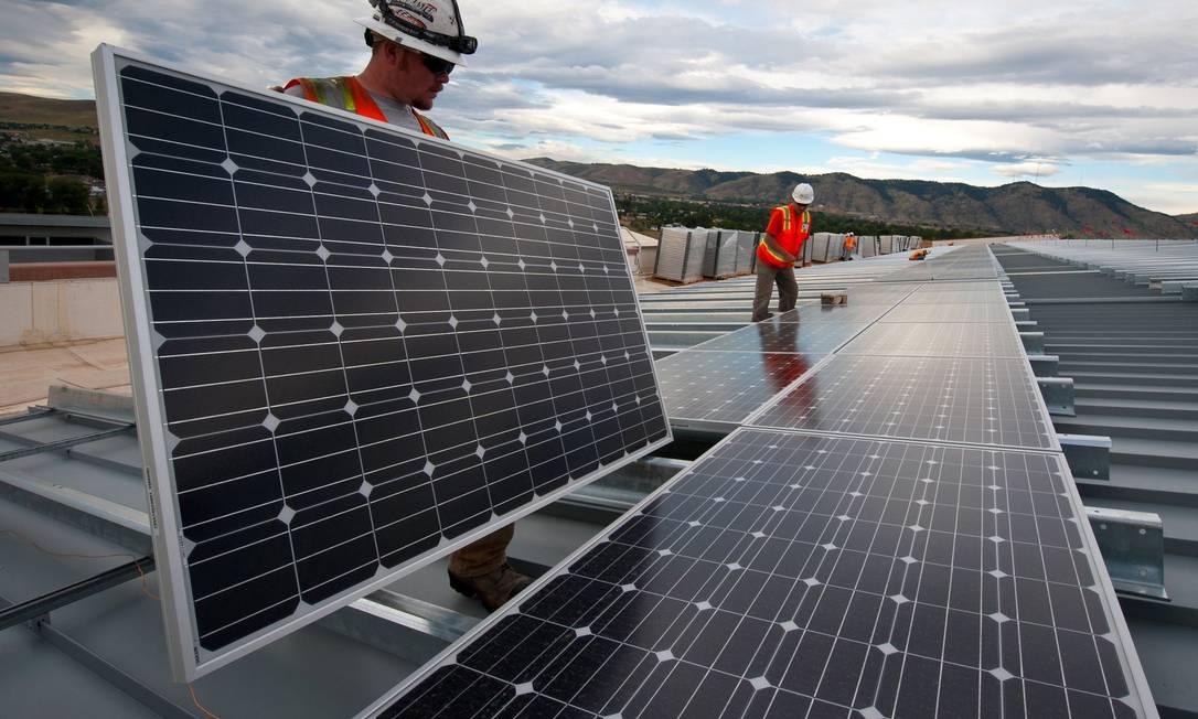 Técnicos instalam painéis de energia solar no teto de edificação comercial em Golden, no Colorado (EUA) Foto: Dennis Schroeder / NREL/CC