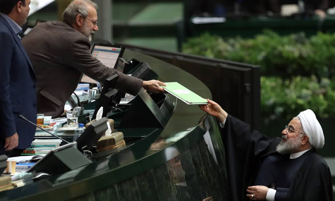 Presidente do Parlamento iraniano, Ali Larijani (E), recebe do presidente Hassan Rouhani o orçamento para o ano fiscal iniciado em março de 2020, no dia 8 de dezembro. Parlamentar não vai tentar mais um mandato na eleição do ano que vem Foto: STR / AFP