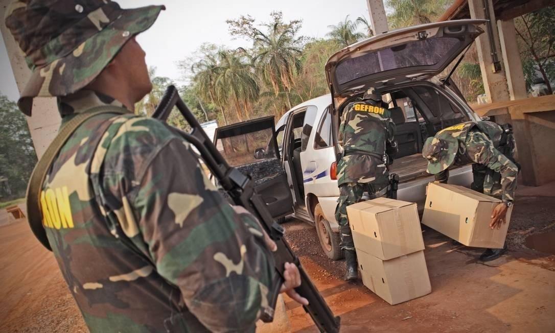Policiais do Grupamento Especial de Fronteira inspecionam veículo prestes a deixar o país Foto: André Coelho/Agência O Globo
