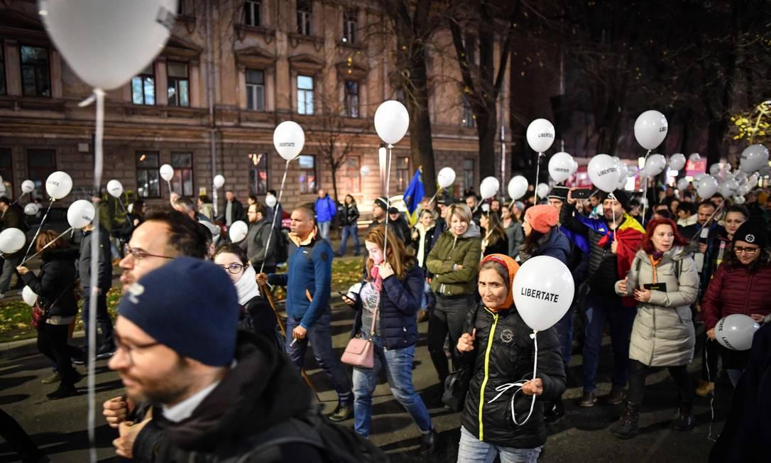 Multidão marcha em Bucareste para homenagear as vítimas da revolução de 1989, que marcou o fim do regime de Nicolae Ceausescu mas cujas circunstâncias até hoje estão pouco claras Foto: DANIEL MIHAILESCU / AFP