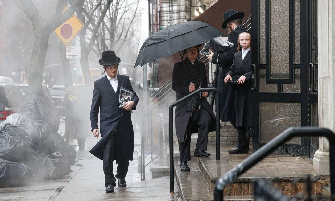 Homens chegam a uma sinagoga ortodoxa no Brooklyn, na cidade de Nova York, em 30 de dezembro de 2019, dois dias depois que um invasor feriu cinco pessoas na casa de um rabino durante uma reunião para celebrar o festival judaico de Hanucá Foto: KENA BETANCUR / AFP