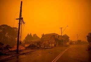 Restos de construções incendiadas ao longo da rua principal da cidade de Cobargo, em Nova Gales do Sul, depois que incêndios devastaram a cidade Foto: SEAN DAVEY / AFP