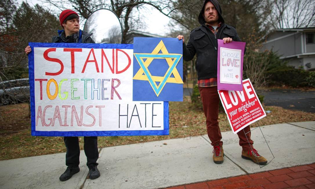 Manifestantes levantam cartazes contra crimes de ódio em frente à casa do rabino Chaim Rottenberg após ataque a faca durante a celebração do Hanucá Foto: KENA BETANCUR / AFP