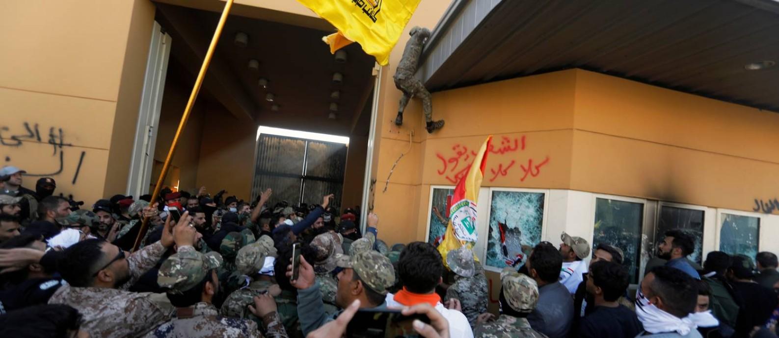 Manifestantes e integrantes das Forças de Mobilização Popular, que reúne milícias xiitas iraquianas, chegam ao portão da embaixada americana em Bagdá Foto: KHALID AL-MOUSILY / REUTERS