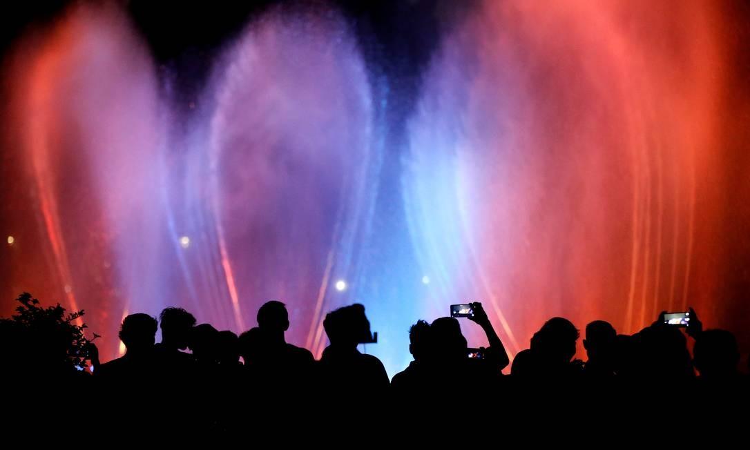 As pessoas assistem a um show na água no complexo do Monumento Nacional (Monas) durante as celebrações da véspera de Ano Novo em Jacarta, na Indonésia Foto: Willy Kurniawan / Reuters