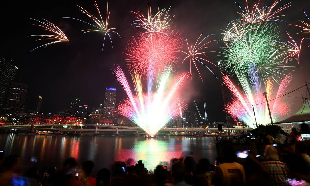 Multidão assiste a fogos de artifício durante as celebrações da véspera de Ano Novo em Brisbane, na Austrália Foto: Dan Peled / Reuters
