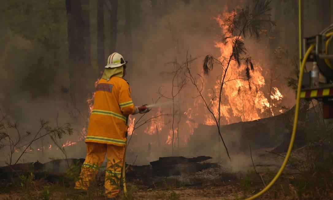 Bombeiros controlam fogo no estado de Nova Gales do Sul, na Austrália. Foto: PETER PARKS / AFP