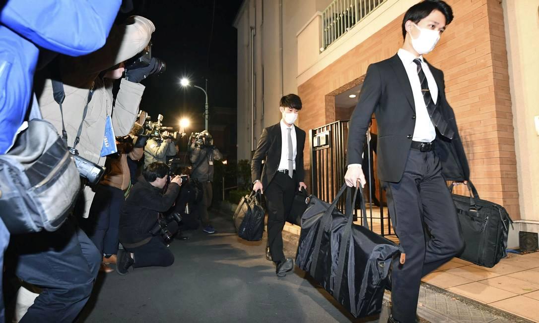 Oficiais do Ministério Público do Distrito de Tóquio carregam algumas malas após invadir a residência de Carlos Ghosn em Tóquio Foto: Kyodo / via Reuters