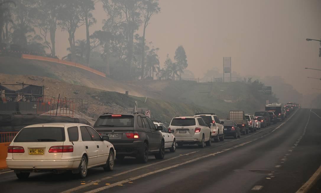 Fila de carros toma conta de rodovia na saída da cidade de Batemans Bay, na Nova Gales do Sul, na direção Norte da Austrália nesta quinta-feira Foto: PETER PARKS / AFP