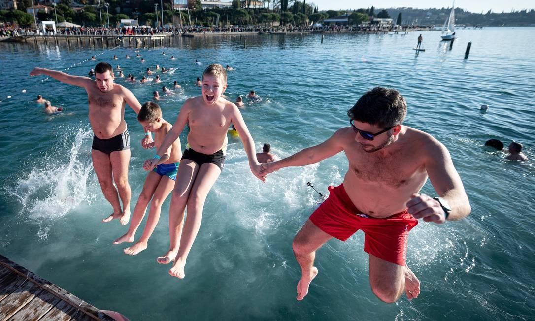 Pessoas pulam em grupo no Mar Adriático, em Portoroz, na Eslovênia. O dia de sol proporcionou temperatura atmosférica máxima de 12°C e muita alegria Foto: Jure Makovec / AFP