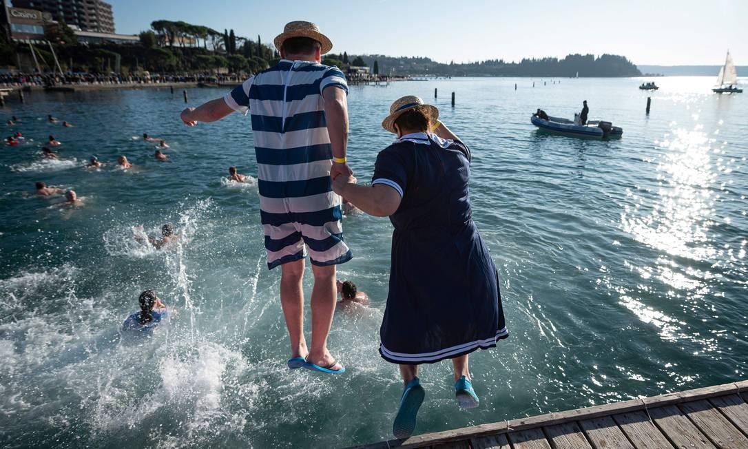 Um casal participa do tradicional banho de ano novo no Mar Adriático com trajes de banho retrô Foto: Jure Makovec / AFP