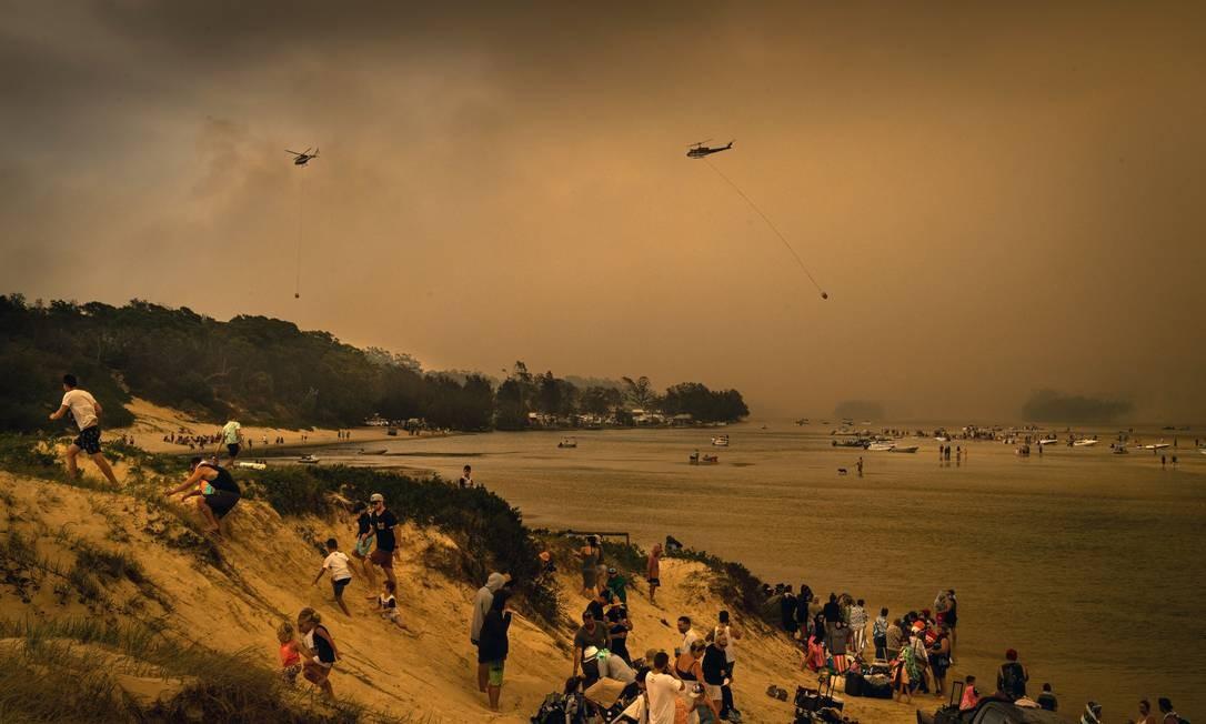 Turistas no Lago Conjola, um popular destino de férias na Austrália, refugiam-se na praia dos incêndios florestais. No ar, se vê helicópteros transportando bolsões de água para combater chamas Foto: Matthew Abbott / The New York Times