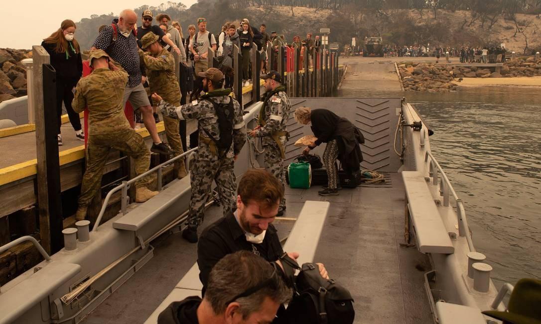 Foto divulgada pela Marinha Real Australiana mostra pessoas sendo evacuadas de Mallacoota. As forças armadas australianas começaram a evacuação marítima de centenas de pessoas presas em uma cidade do sudeste cercada pelo fogo nesta sexta-feira Foto: Helen Frank / AFP