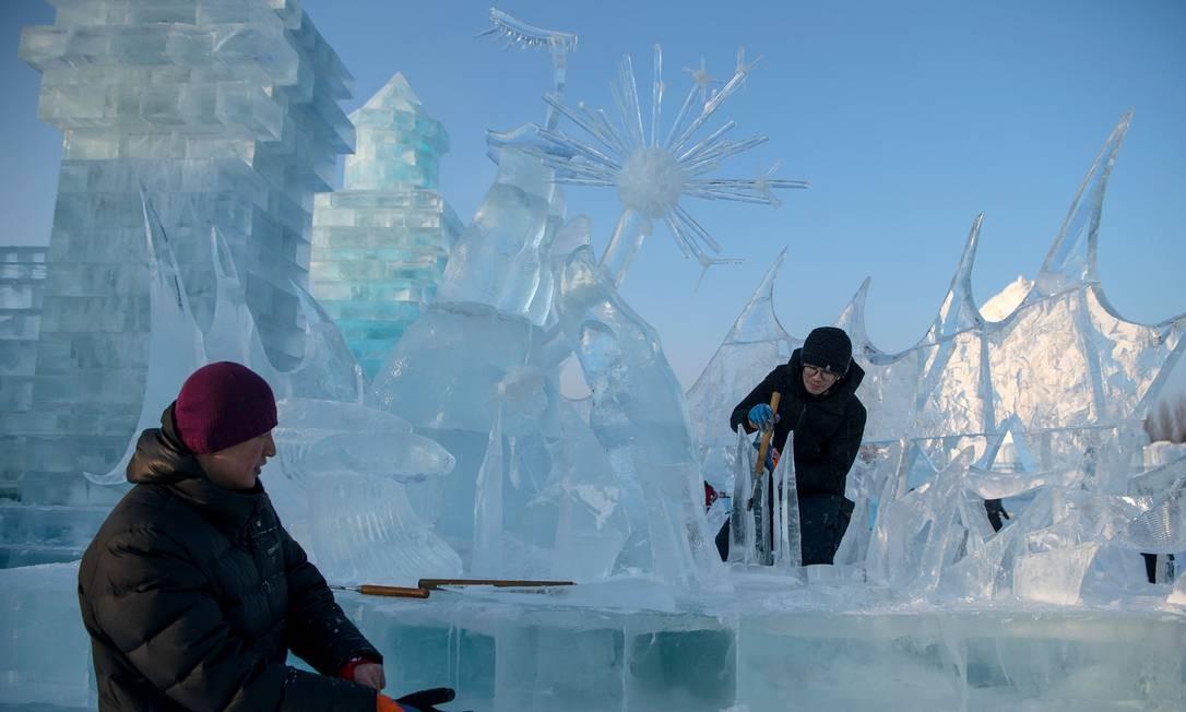 Escultores de gelo dão retoques finais em uma escultura de gelo no festival Harbin Ice and Snow World em Harbin, na província de Heilongjiang, no nordeste da China, em 3 de janeiro de 2020. (Foto de NOEL CELIS / AFP) Foto: Noel Celis / AFP