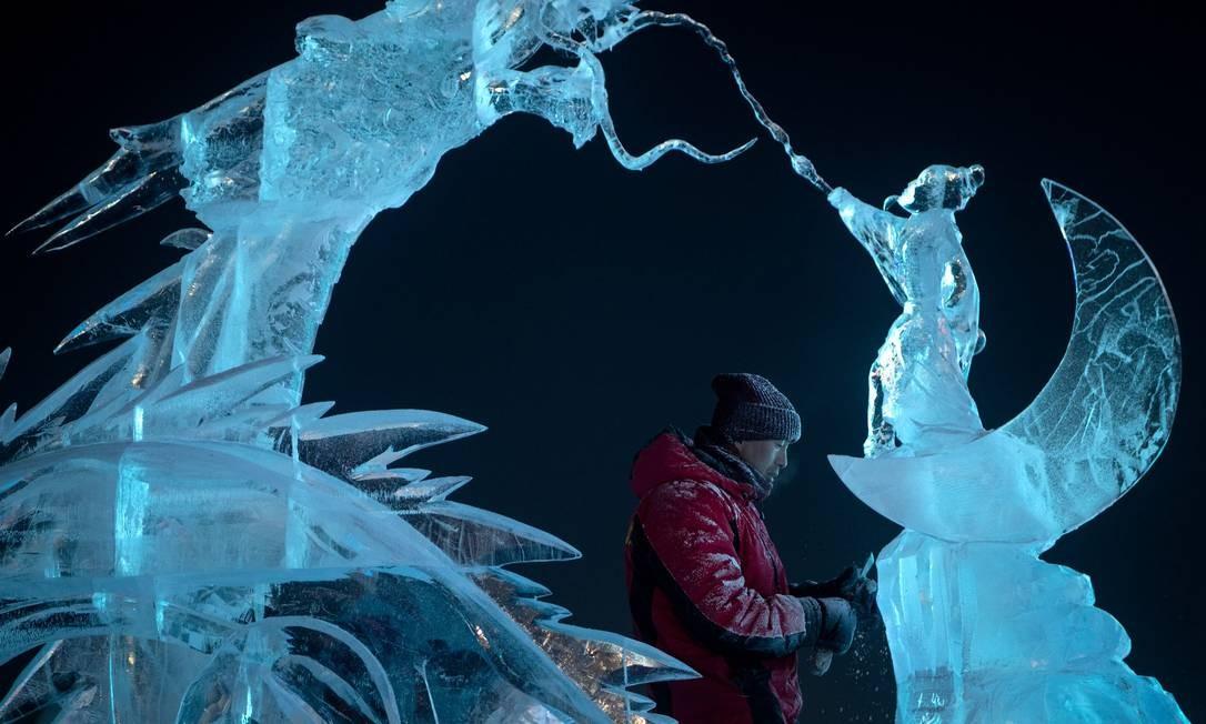 Um escultor de gelo dá os retoques finais em uma escultura de gelo Foto: Noel Celis / AFP