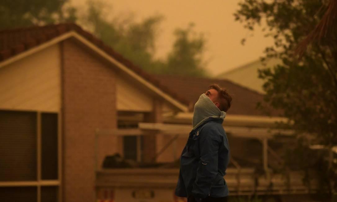 Morador de Nowra, em New South Wales, se protege da fumaça com toalha enrolada no rosto Foto: Tracey Nearmy/Reuters / Tracey Nearmy/Reuters