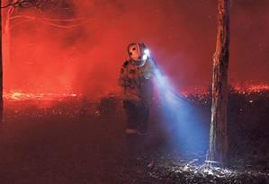 Um bombeiro procura brasas ocultas numa floresta calcinada para evitar que o fogo destrua casas na cidade de Nowra, em Nova Gales do Sul. Incêndios florestais maiores e mais frequentes ameaçam economia e saúde Foto: SAEED KHAN/AFP/31-12-2019