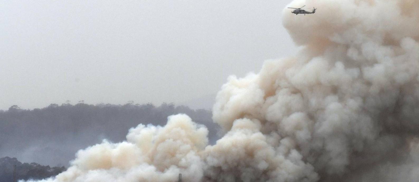 Helicóptero militar sobrevoa incêndio em mata próximo à cidade de Eden, no estado de Nova Gales do Sul, nesta segunda-feira (6) Foto: SAEED KHAN / AFP
