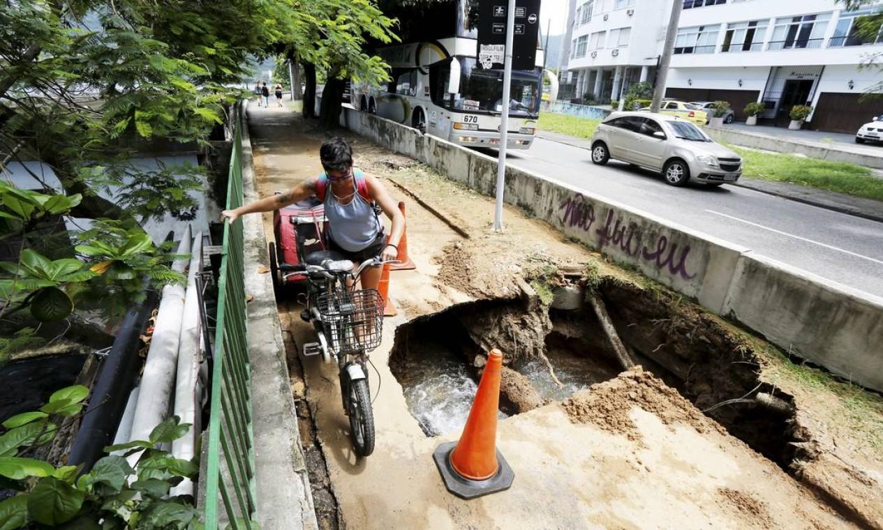 Ciclista passa por cantinho para não cair na cratera na orla da Lagoa Foto: Guilherme Pinto / Agência O Globo