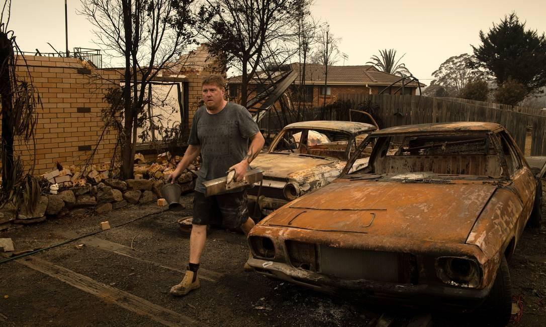 Michael Fletcher visita a casa da sua familia, destruída pelos incêncios florestais em Conjola Park, Austrália Foto: MATTHEW ABBOTT / NYT