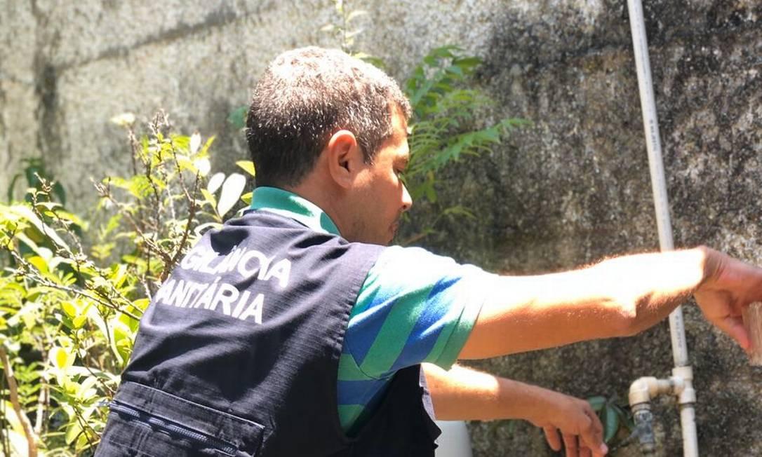 Agente da Vigilância Sanitária do município coleta amostra de água da Cedae para análise microbiológica Foto: Divulgação