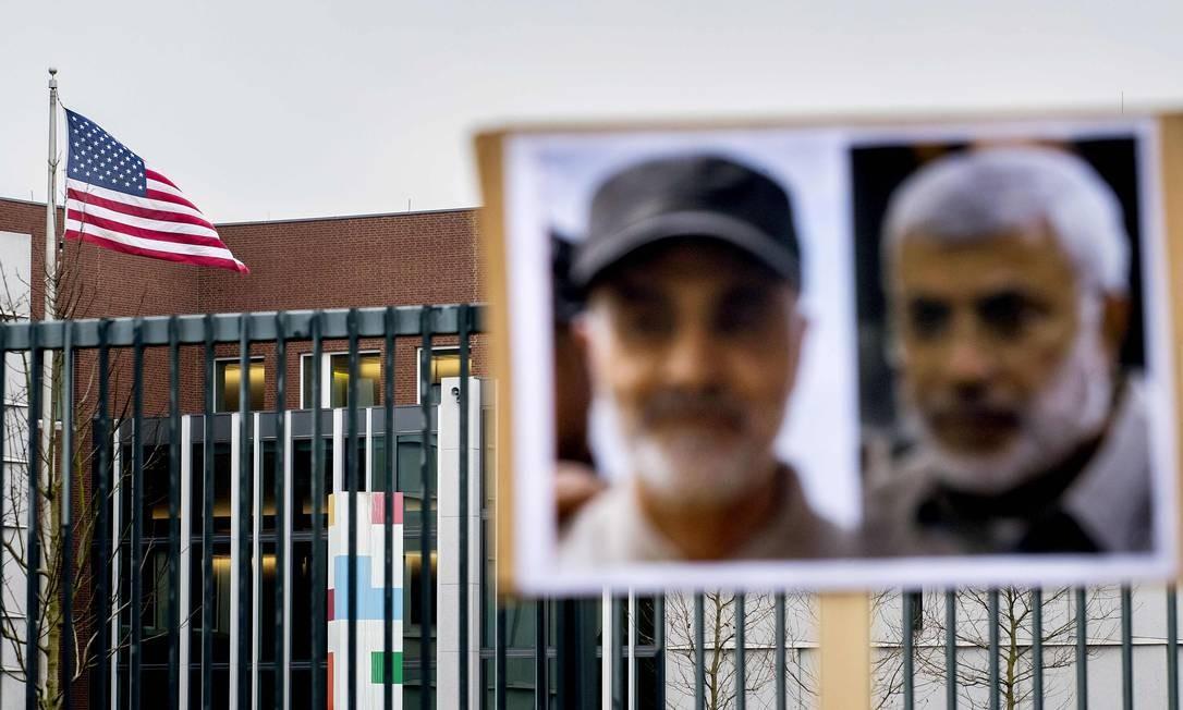 Fotos do general iraniano Qasem Soleimani (E) e do vice-líder de milícia pró-Irã no Iraque Abu Mahdi al-Muhandis, mortos na semana passada em Bagdá, penduradas diante da embaixada americana em Haia, na Holanda Foto: KOEN VAN WEEL / AFP