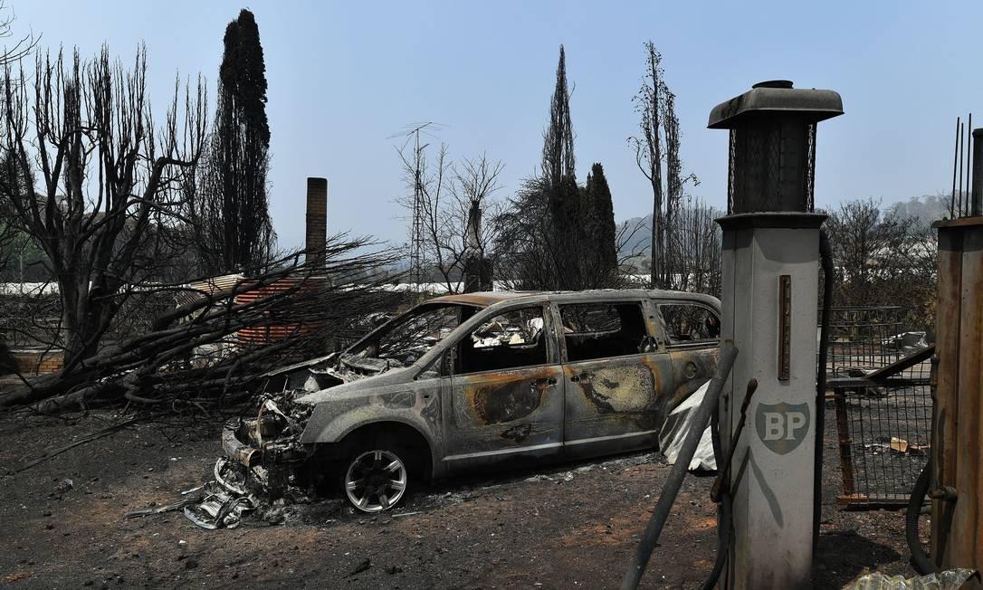 Carro foi destruído pelo fogo na entrada de uma propriedade em Batlow, no estado australiano de Nova Gales do Sul Foto: SAEED KHAN / AFP