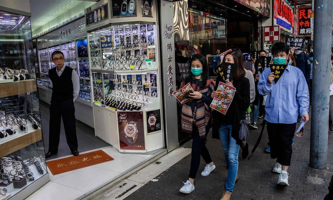 Preocupados com a epidemia, os moradores de Hong Kong correram para comprar máscaras respiratórias, vendidas em farmácias. Foto: ISAAC LAWRENCE / AFP