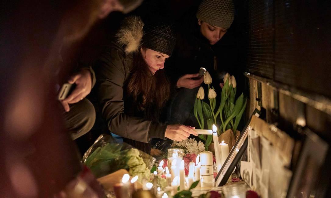 Altar foi improvisado com velas e fotos das vítimas do voo 752 em vigília na Mel Lastman Square, em Toronto Foto: Geoff Robins / AFP