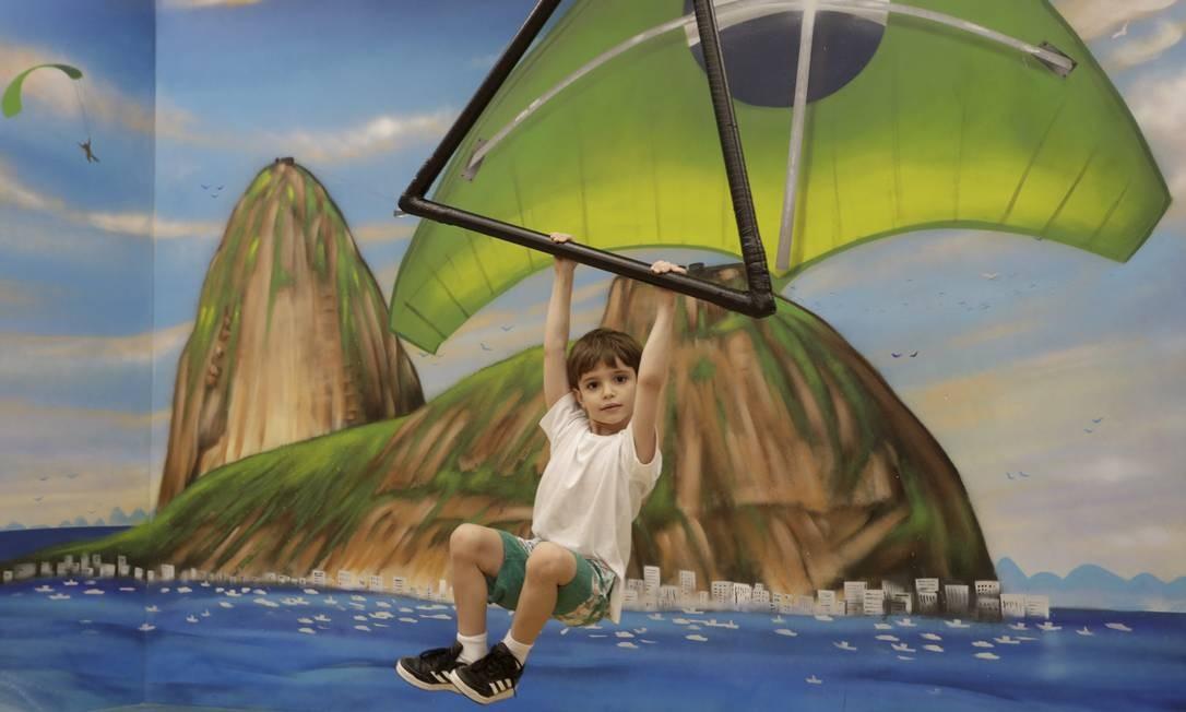 O menino Gabriel, de 5 anos, se diverte 'voando' de asa delta pelo Rio, com o Pão de Açúcar ao fundo Foto: Domingos Peixoto / Agência O Globo