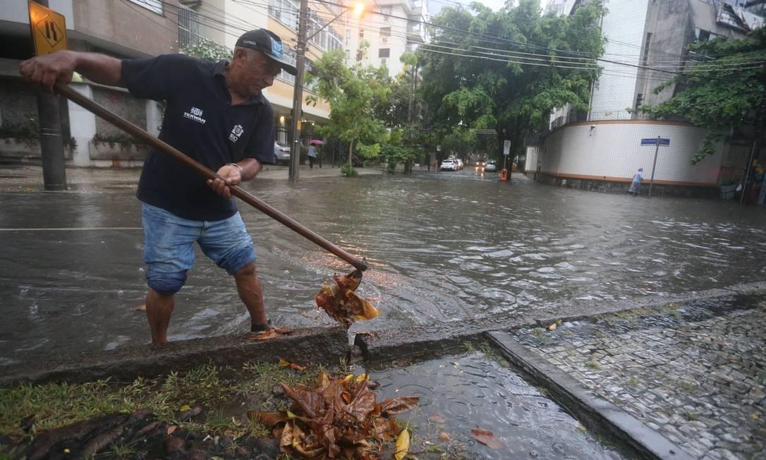 Homem tenta desobstruir bueiro na esquina das ruas Abelardo Lobo e Professor Saldanha, na Lagoa Foto: Fabiano Rocha / Agência O Globo