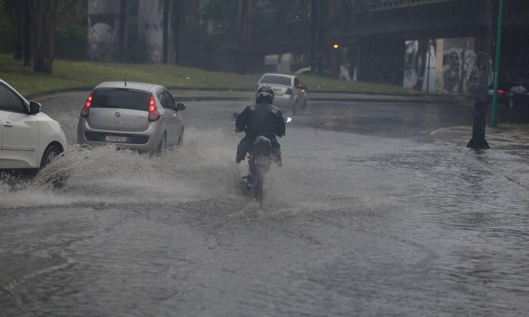Motociclista passa por rua alagada na Lagoa Foto: Fabiano Rocha / Agência O Globo