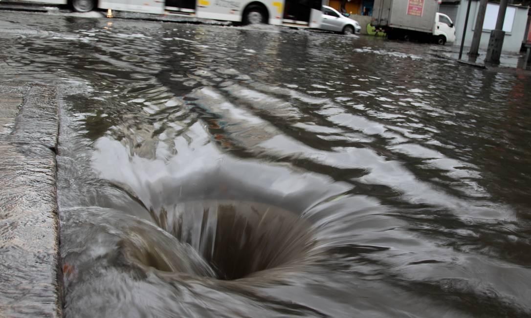 Tampa de bueiro é retirada e redemoinho se forma com o escoamento da água da chuva Foto: Gabriel de Paiva / Agência O Globo