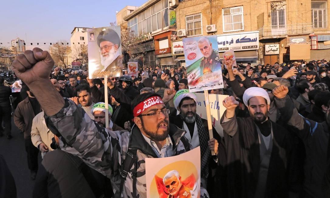 Manifestantes carregam imagem de Soleimani e do líder supremo aiatolá Ali Khamenei durante manifestação conservadora pró-regime em frente à embaixada britânica Foto: ATTA KENARE / AFP