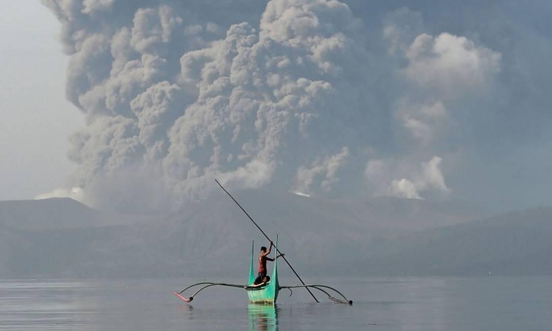 Jovem que vive nas margens do vulcão navega com canoa na cidade de Tanauan, na província de Batangas, a sul de Manila Foto: TED ALJIBE / AFP