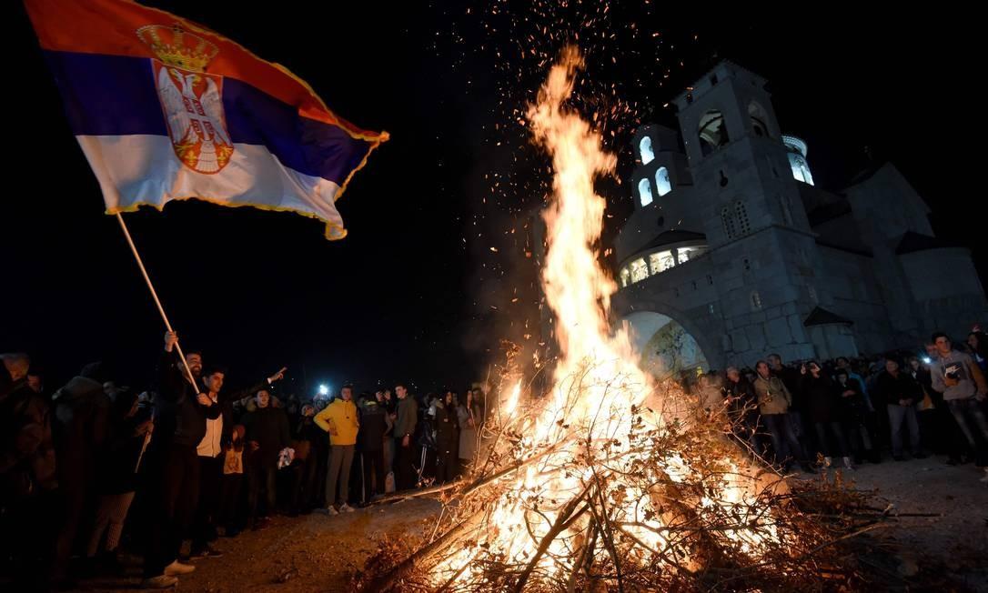 Católicos ortodoxos montenegrinos agitam a bandeira sérvia durante cerimônia em frente a uma igreja na capital Podgorica, para marcar o Ano Novo Cristão Ortodoxo, nesta terça Foto: Savo Prelevic / AFP