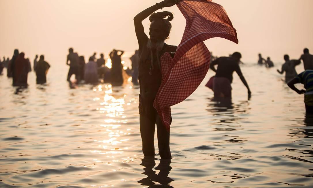 Um hindu Sadhu dá um mergulho sagrado na Baía de Bengala durante o Gangasagar Mela, na ilha de Sagar, cerca de 150 quilômetros ao sul de Calcutá, Índia Foto: Xavier Galiana / AFP