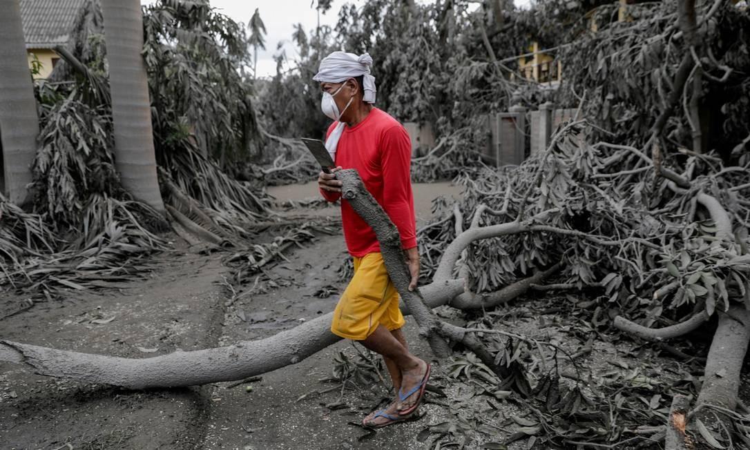 Trabalhador carrega um galho caído em um resort coberto de cinzas vulcânicas em Talisay, Batangas, Filipinas, nesta terça Foto: Eloisa Lopez / REUTERS
