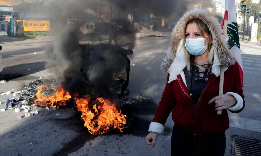 Manifestante libanesa ao lado barricada em chamas de pneu durante uma manifestação em Beirute, nesta terça Foto: Anwar Amro / AFP