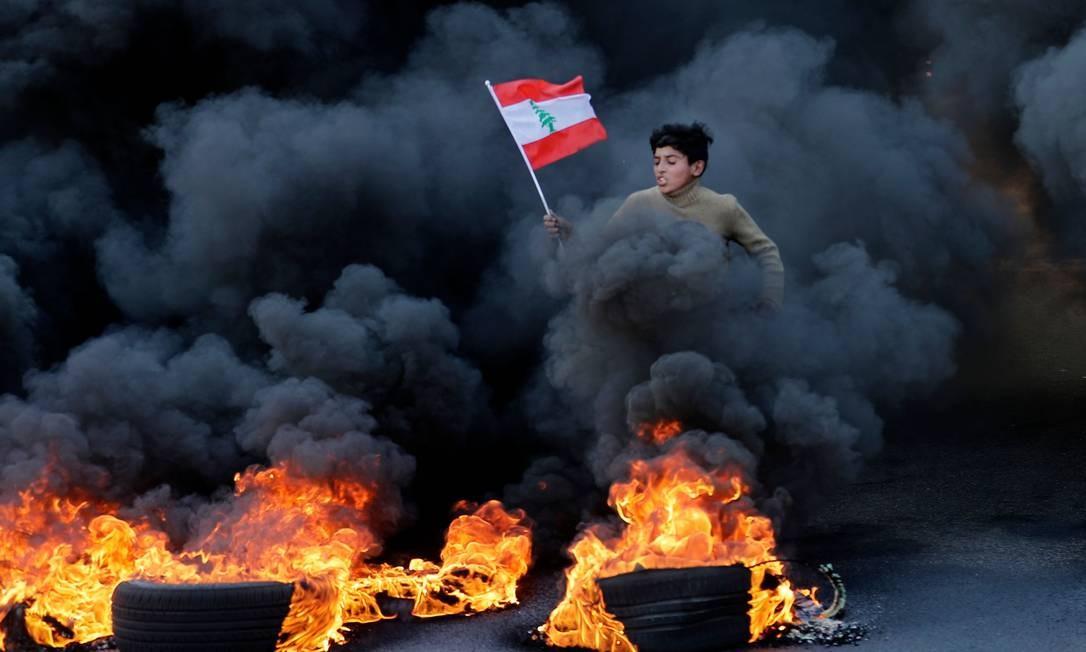 Jovem libanês corre com uma bandeira nacional enquanto a fumaça sobe com a queima de pneus durante uma manifestação na área de Jal el-Dib, nos arredores do norte de Beirute Foto: Joseph Eid / AFP