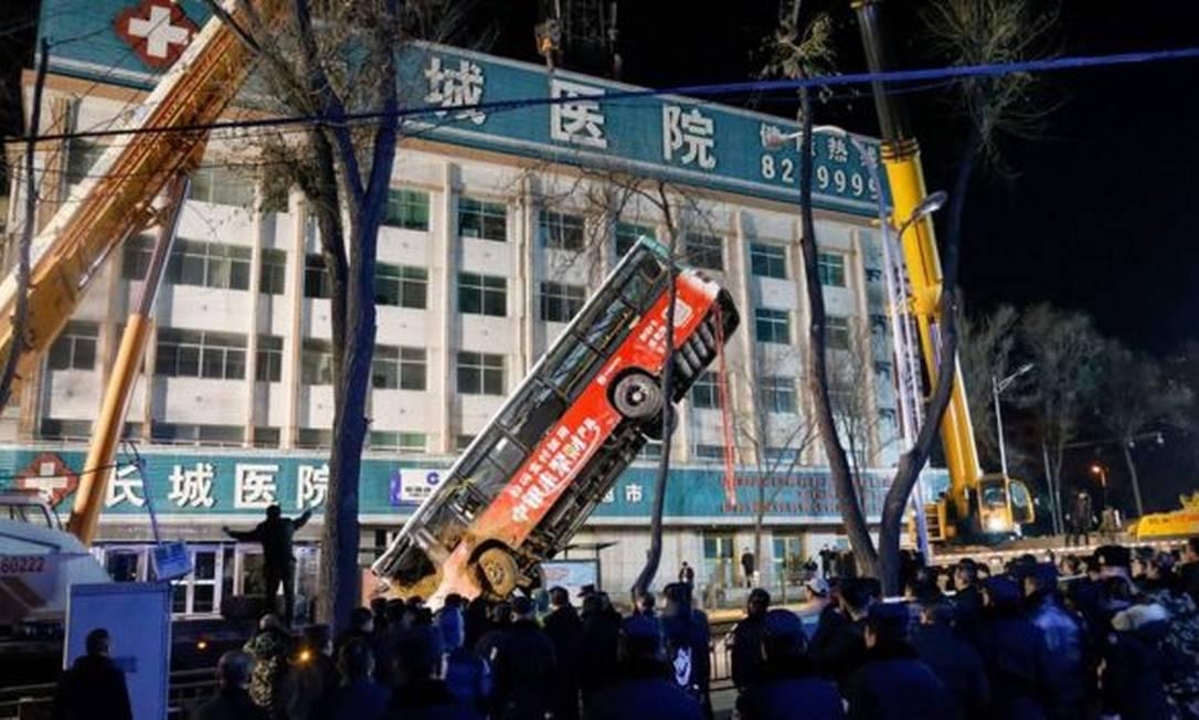 Ônibus que caiu em buraco na China, resultando em seis mortes, é retirado por equipes de resgate Foto: AFP