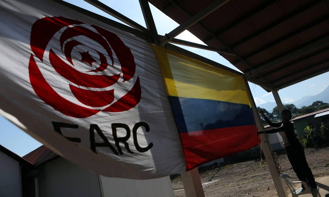 Mulher pendura bandeira da Colômbia ao lado de bandeira do partido político das Farc, em Pondores Foto: LUISA GONZALEZ / Reuters/01-08-2019