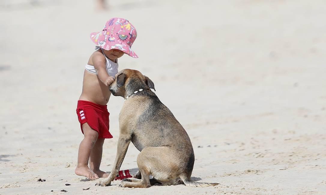 Uma criança brinca com um cão na praia do Leme. Liberação de cachorros na orla carioca divide opinião de banhistas Foto: Márcio Alves / Agência O Globo