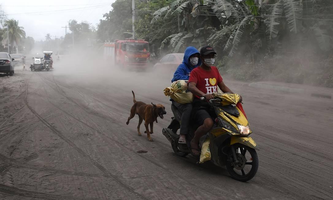 Cão de estimação segue os donos motociclistas, que se protegem da poeira tóxica com máscaras, por uma estrada coberta de cinzas vulcânicas na cidade de Agoncillo, província de Batangas, ao sul de Manila, nesta quarta. Autoridades filipinas tentam evitar que milhares de pessoas retornem às suas casas em áreas ameaçadas por uma nova erupção do vulcão Taal Foto: Ted Aljibe / AFP